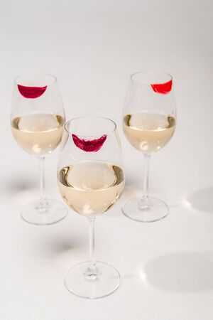 lipstick prints on champagne glasses with alcohol on white Фото со стока