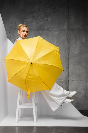 beautiful young woman sitting on chair and holding yellow umbrella on white and grey Reklamní fotografie