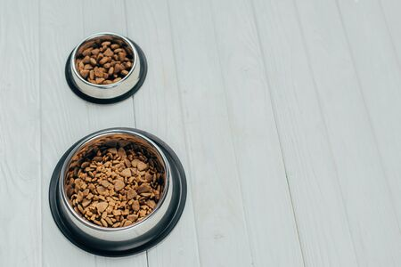 metal bowls with pet food on white wooden surface