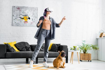 girl with colorful hair and VR headset standing near dog in living room Stock Photo