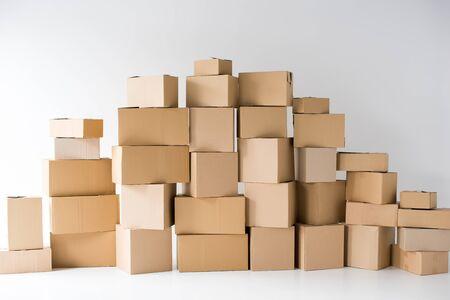 braune Kartons übereinander gestapelt auf weiß