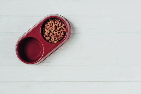 top view of bowl with dog food on white wooden surface Stock Photo