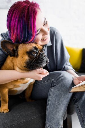 girl with colorful hair hugging bulldog, smiling and holding book