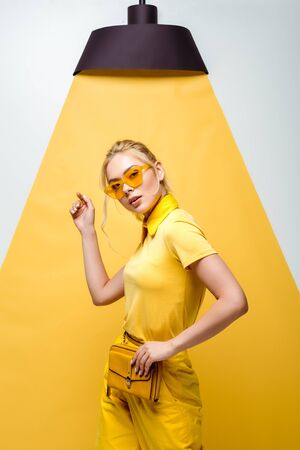 attractive blonde woman in sunglasses looking at camera and gesturing on white and yellow