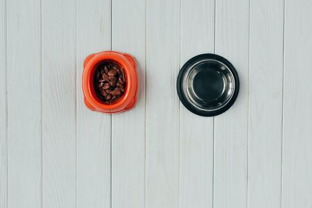 top view of bowl with pet food and empty bowl on wooden surface with copy space Stock Photo