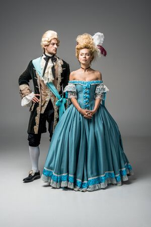 attractive victorian woman in blue dress near handsome man with hand on hip on grey
