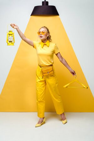 attractive blonde woman in sunglasses holding hanger and retro lamp on white and yellow Stock Photo