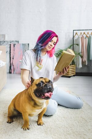 selective focus of beautiful girl with colorful hair reading book and sitting on floor near French bulldog