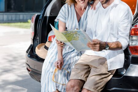 cropped view of woman standing near man with map in hands near car