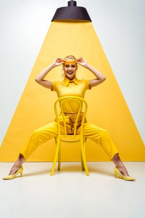 cheerful blonde woman touching sunglasses and sitting on chair on white and yellow