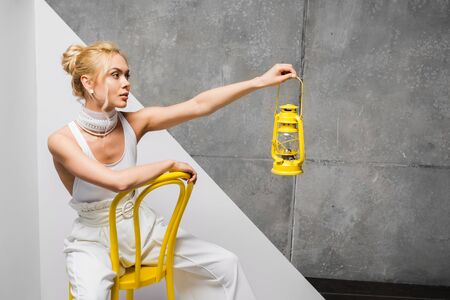 stylish blonde woman sitting on yellow chair and holding retro lamp on white and grey