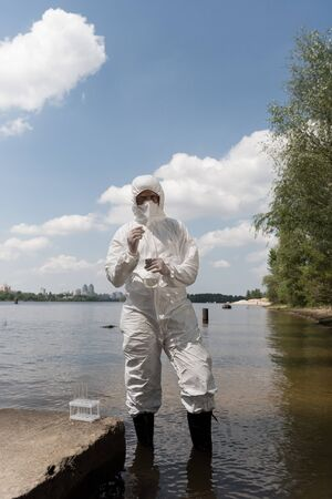 full length view of water inspector in protective costume, latex gloves and respirator holding flask with water sample at river