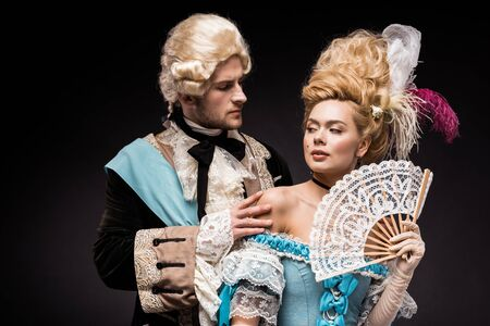 handsome man looking at young victorian woman in wig holding fan on black