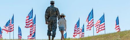 panoramic shot of father in military uniform holding hands with daughter near american flags