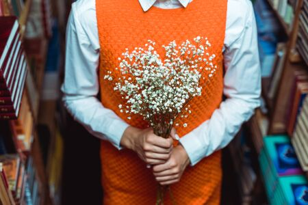 cropped view of woman in orange dress holding white flowers in library Stock Photo