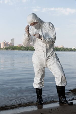 full length view of water inspector in protective costume and latex gloves taking water sample 写真素材