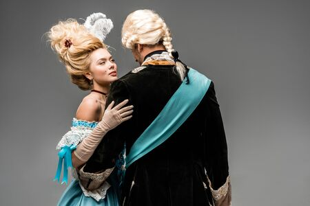 attractive victorian woman in blue dress hugging man in wig on grey Stock Photo