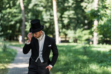 handsome young victorian man touching hat and standing with hand in pocket outside