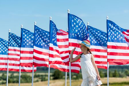 happy patriotic child standing in white dress near american flags and waving hand