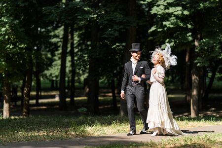 happy young victorian woman and handsome man in hat walking outside