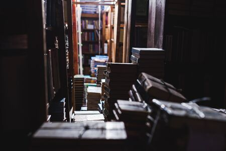 selective focus of vintage books on shelves in library