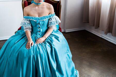 Ausgeschnittene Ansicht einer viktorianischen Frau, die auf einem antiken Stuhl sitzt