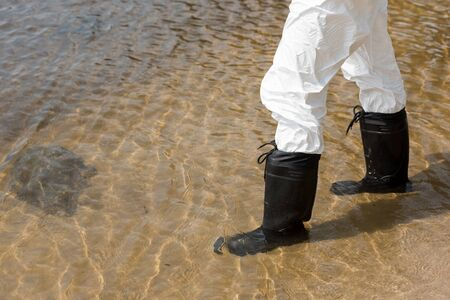 cropped view of water inspector in protective costume and boots standing in river Foto de archivo - 127994378