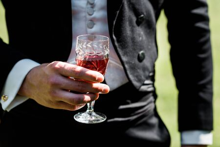 cropped view of victorian man in suit holding wine glass with drink