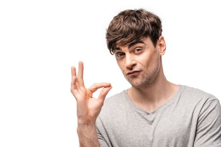 handsome young man showing shut up sign and looking at camera isolated on white