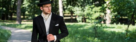panoramic shot of handsome victorian man in hat standing outside