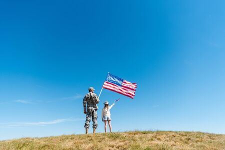 back view of kid in straw hat and military father holding american flags