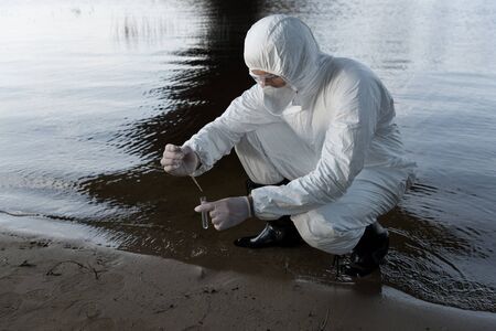 water inspector in protective costume and respirator taking water sample at river