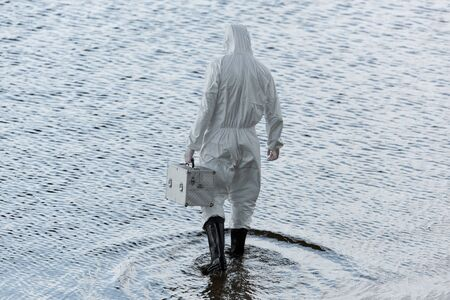 back view of water inspector in protective costume holding inspection kit in river Foto de archivo - 127994510