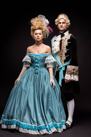 handsome victorian man and woman in wigs standing on black