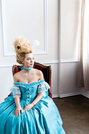 beautiful victorian woman in blue dress sitting on antique chair