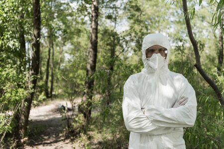 front view of ecologist in protective costume and respirator with crossed arms in forest