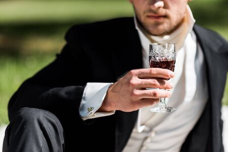 cropped view of victorian man holding wine glass with drink