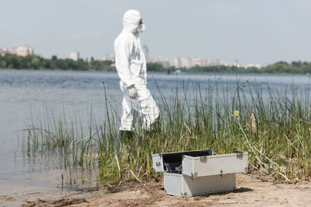 selective focus of water inspector in protective costume and inspection kit on foreground Stock Photo