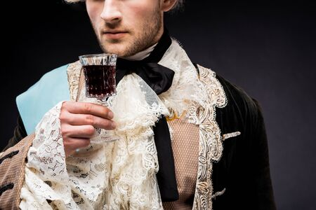 cropped view of victorian man holding wine glass on black