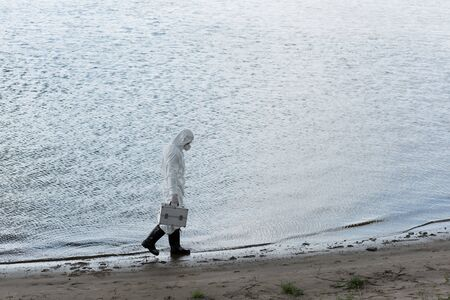 full length view of water inspector in protective costume and respirator holding inspection kit while walking on river coast 写真素材