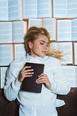 attractive and blonde woman with closed eyes lying and holding book Banco de Imagens