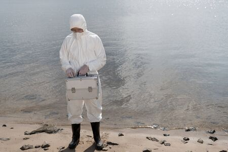 full length view of water inspector in protective costume holding inspection kit at river coast