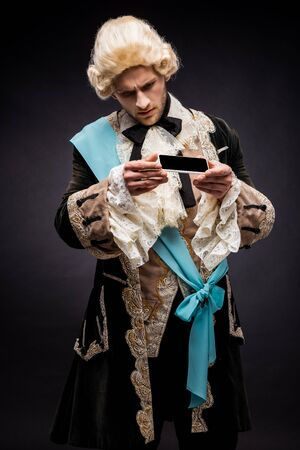 handsome victorian man in wig looking at smartphone with blank screen on black