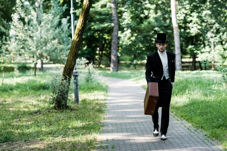 handsome victorian man in hat holding baggage and walking outside Reklamní fotografie