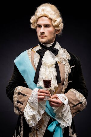 handsome victorian man in wig holding wine glass on black 스톡 콘텐츠