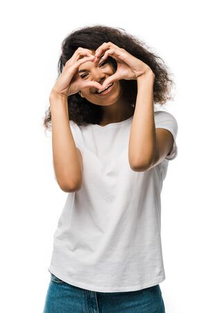 happy african american girl covering face while showing heart with hands isolated on white Stockfoto