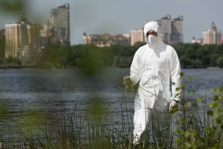 selective focus of water inspector in protective costume, respirator and goggles holding flask with water sample Stock Photo