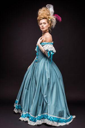 Jolie femme victorienne en perruque debout en robe bleue sur fond noir