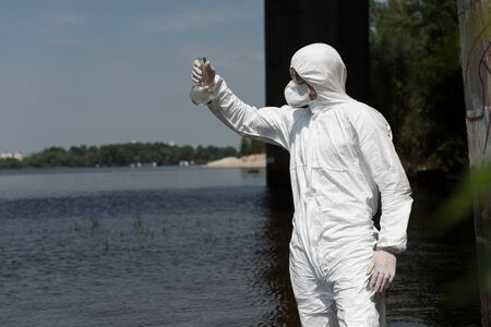 water inspector in protective costume holding flask with water sample at river Stock Photo
