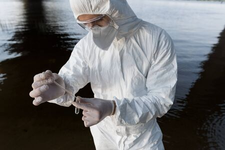 partial view of water inspector in respirator and goggles taking water sample Stock Photo